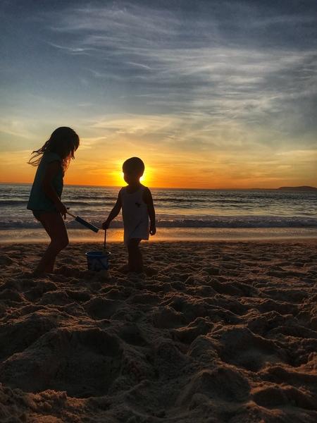 Kids playing on the beach in sunset by Anita Varga