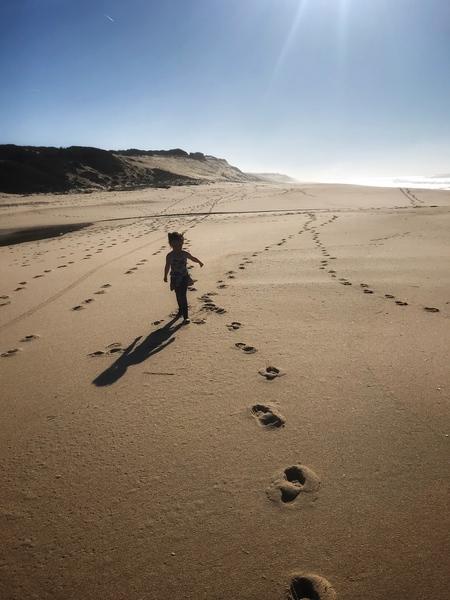 A girl in a huge sandy Atlantic coast of Portugal by Anita Varga