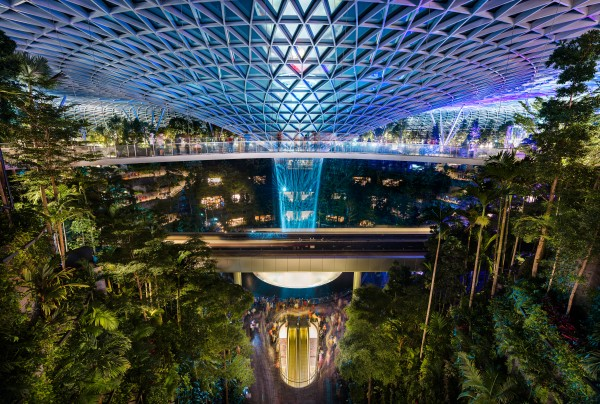 The Jewel at Changi Airport with the rain vortex indoor waterfall illuminated during the light show Singapore by Em Campos