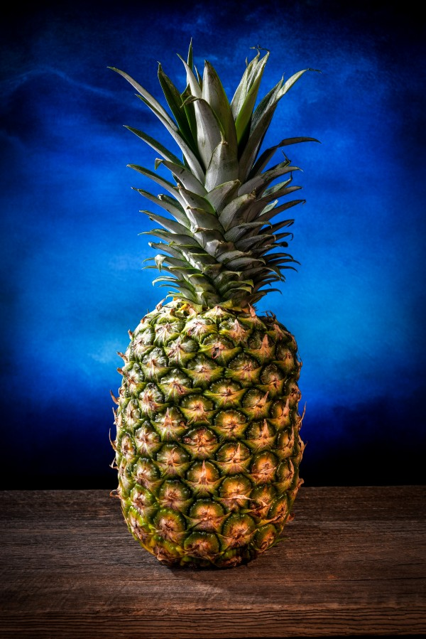 Big pineapple with its leaves on a barn wood board with a blue background by Francois Lariviere