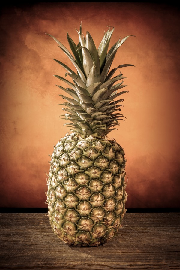 Big pineapple with its leaves on a barn wood board by Francois Lariviere
