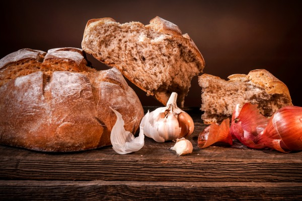 Country bread garlic cloves and French shallots on a barn wood board by Francois Lariviere