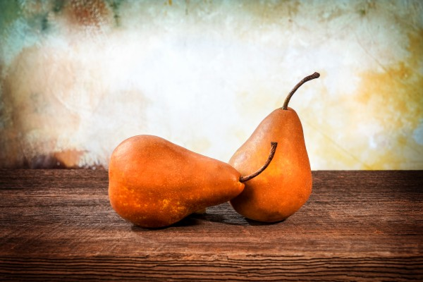 Two large yellow bosc pears on a barn wood table by Francois Lariviere
