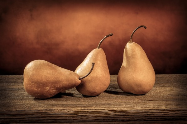 Three large yellow bosc pears on a barn wood table by Francois Lariviere