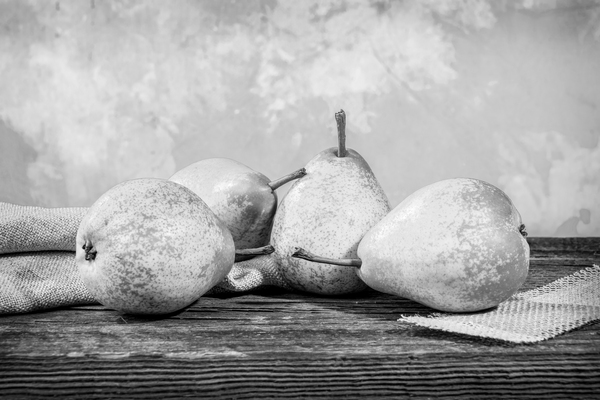 Four yellow pears and a fern on a barn wood table in front of a backdrop black and white by Francois Lariviere