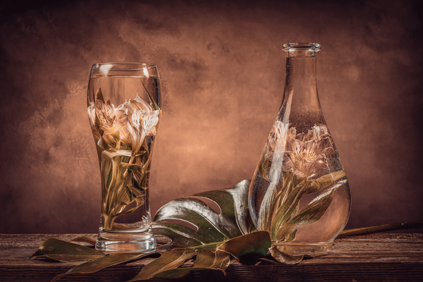 Cut flowers and tropical plants in a glass of water on a barn wood table Filter effect brown sepia by Francois Lariviere