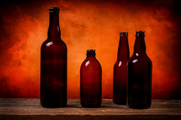 Four dark brown glass beer bottles on a barn wood table in front of an orange background by Francois Lariviere