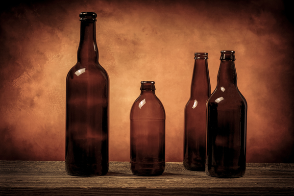 Four dark brown glass beer bottles on a barn wood table filter effect brown sepia by Francois Lariviere