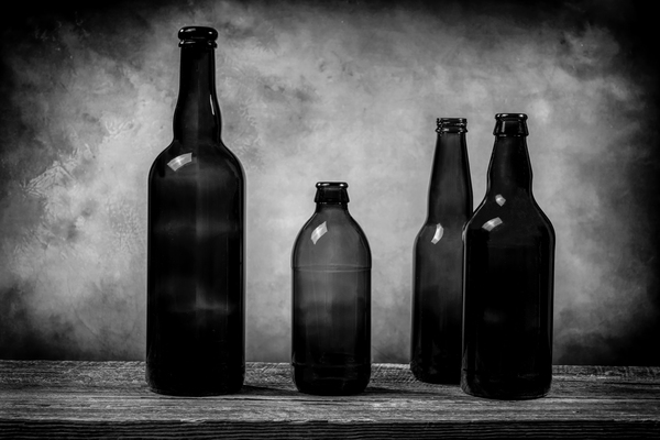 Four dark brown glass beer bottles on a barn wood table in front Black and White by Francois Lariviere