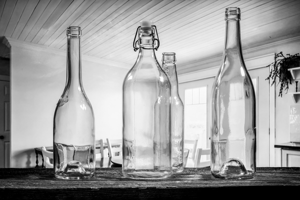 Four transparent glass bottles on a barn wood table black and white by Francois Lariviere