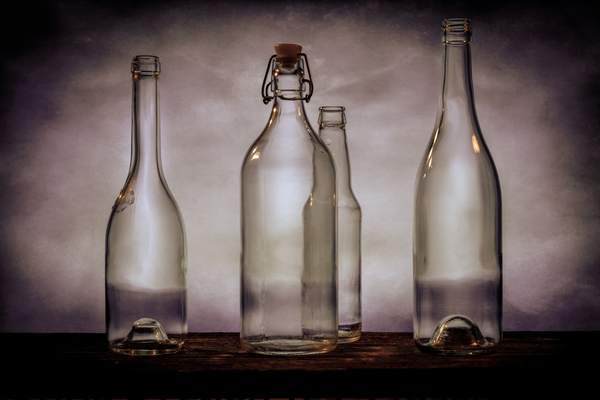 Four dark brown glass beer bottles on a barn wood table black and white by Francois Lariviere