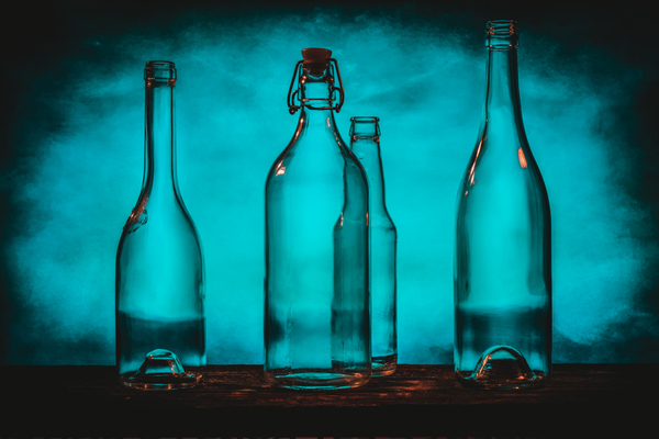 Four transparent glass bottles on a barn wood table in front of a blue background by Francois Lariviere