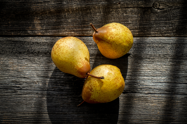 Three yellow pears on a barn wood plank table with shadows from the sun by Francois Lariviere