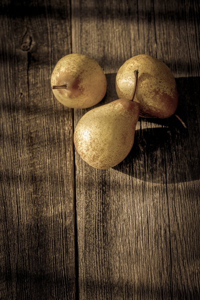 Three yellow pears on a barn wood plank table with shadows from the sun brown filter effect by Francois Lariviere