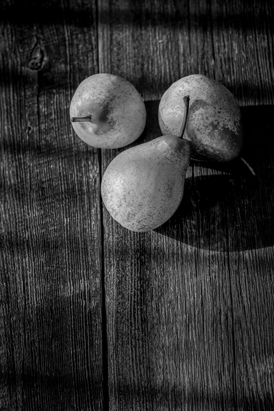 Three yellow pears on a barn wood plank table with shadows from the sun black and white by Francois Lariviere