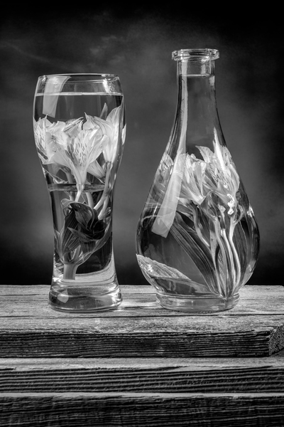 Cut flowers and pink lilies in a vase filled with water on a barn wood table black and white by Francois Lariviere