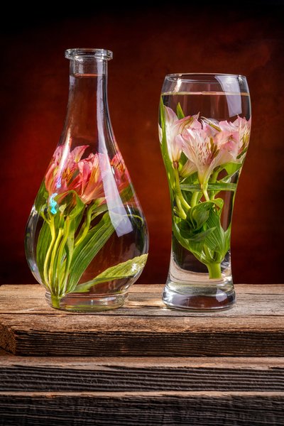 Cut flowers and pink lilies in a vase filled with water on a barn wood table in front of a dark canvas background by Francois Lariviere