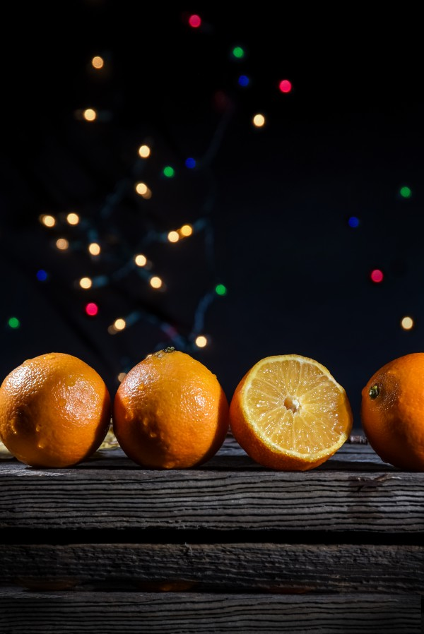 A row of tangerines on a barn wood board with background lights on a black background by Francois Lariviere