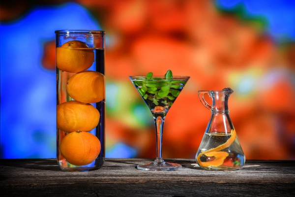 colorful still life of three glass containers with oranges and some green plant leaves by Francois Lariviere