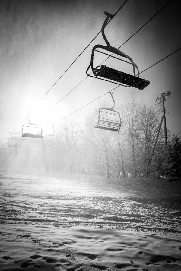 Against day of a ski lift during a snow blizzardblack and white by Francois Lariviere