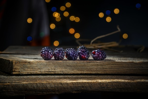 Blackberries in a row on a barn wood board with lights in the background by Francois Lariviere