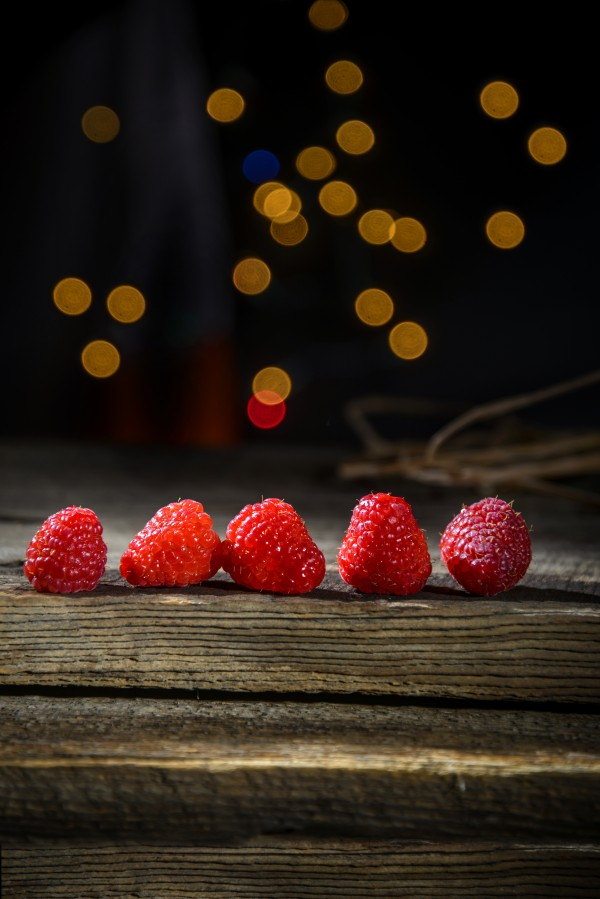 Raspberries in a row on a barn wood board with lights in the background by Francois Lariviere