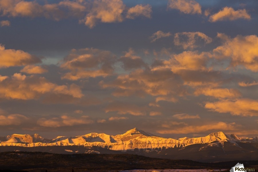 Glowing warmly lit snow covered mountain range and foothills with glowing clouds and blue sky at sunrise; Calgary, Alberta, Canada  Print