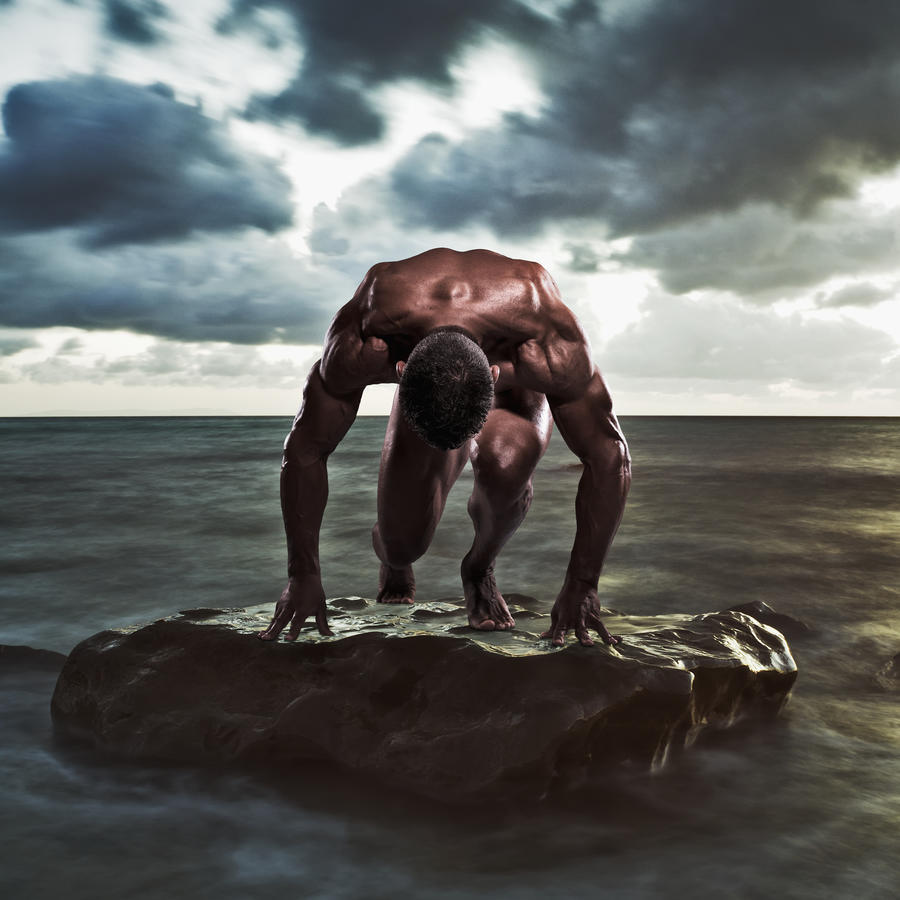 A muscular man in the starting position on a wet rock in the water;Tarifa cadiz andalusia spain  Print