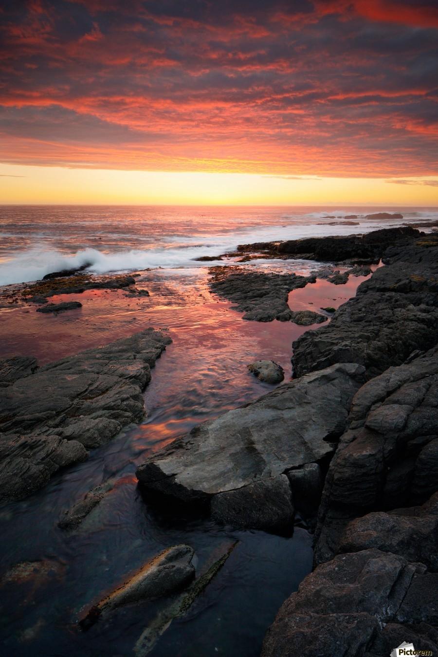 Sunset over rocky coastline  Print