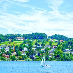 Sailboat On Lake Lucerne with Alpine Village in Background
