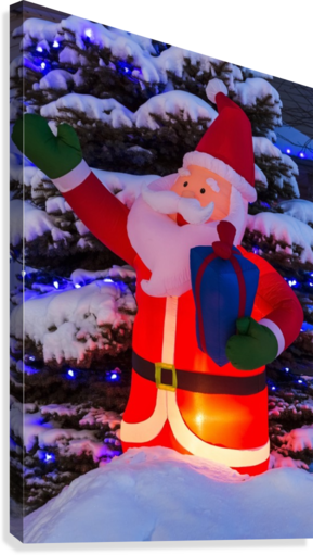 Glowing inflated Santa Claus Christmas decoration with Christmas lights on a snow covered evergreen tree; Calgary, Alberta, Canada  Canvas Print