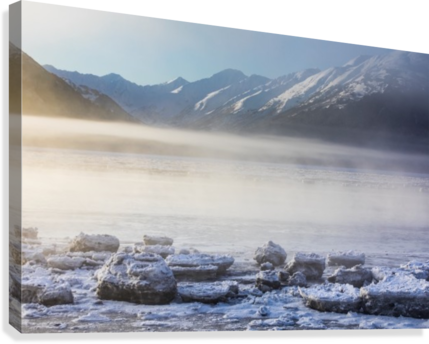 The sun shines through low altitude fog cast in warm light along Turnagain Arm and the Seward Highway, sea ice covering the ocean in the foreground, the Kenai Moutains revealed in the background, South-central Alaska; Alaska, United States of America  Canvas Print