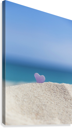 A lavender heart shaped sea glass in the sand at the beach; Honolulu, Oahu, Hawaii, United States of America  Canvas Print