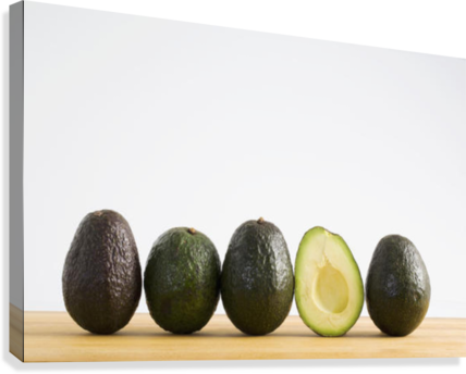 A Row Of Avocados Standing Upright On A Wooden Board With One Cut In Half Without The Pit; Calgary, Alberta, Canada  Canvas Print