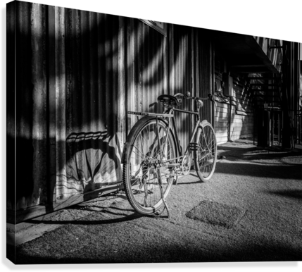 Bicycle parked against the building black and white  Canvas Print