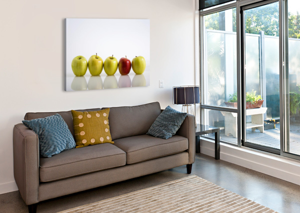 FOUR YELLOW APPLES WITH ONE RED APPLE IN A ROW ON A REFLECTIVE SURFACE; CALGARY, ALBERTA, CANADA PACIFICSTOCK  Canvas Print