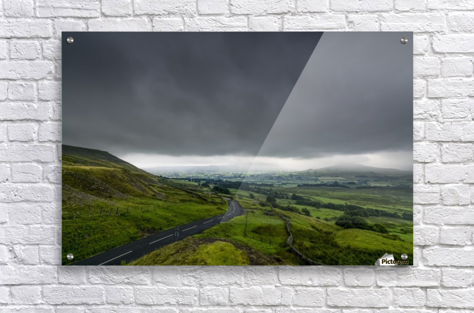 Dark storm clouds over a lush, green landscape and road; North Yorkshire, England  Acrylic Print