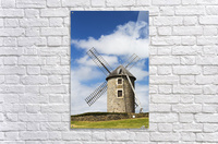 An old stone windmill on a hillside with wooden blades, surrounded by a stone fence with blue sky and clouds; Brehec, Brittany, France  Acrylic Print