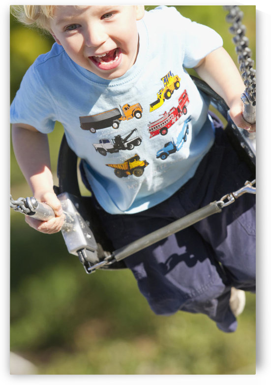 Young Boy Smiling Swinging In A Swing At The Playground. by PacificStock