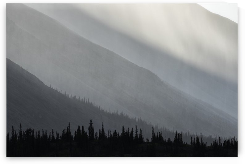 Light shines through the rain as it falls on the mountains along the Wind River in the Peel Watershed; Yukon, Canada by PacificStock