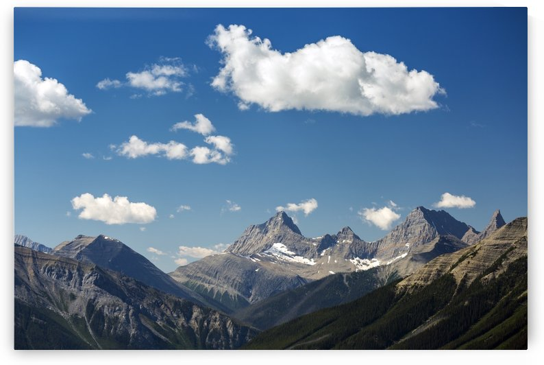 Mountain range with fluffy clouds and blue sky, Banff National Park; Banff, Alberta, Canada by PacificStock