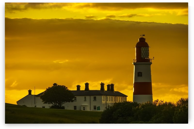 Souter Lighthouse under a glowing golden sky at sunset; South Shields, Tyne and Wear, England by PacificStock
