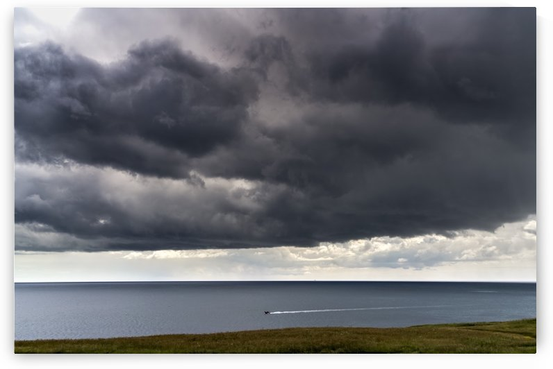 Ominous dark clouds over the ocean and a small boat traveling along the coastline; South Shields, Tyne and Wear, England by PacificStock