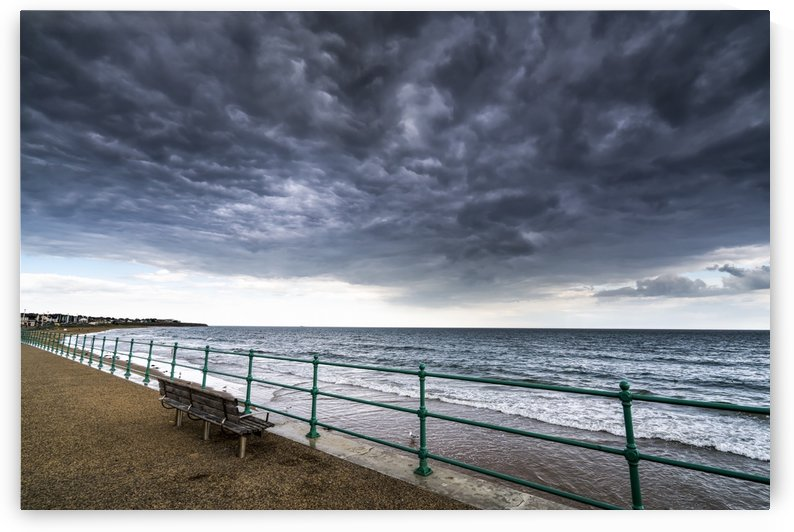 Green metal railing and bench along the water under dark storm clouds; Sunderland, Tyne and Wear, England by PacificStock