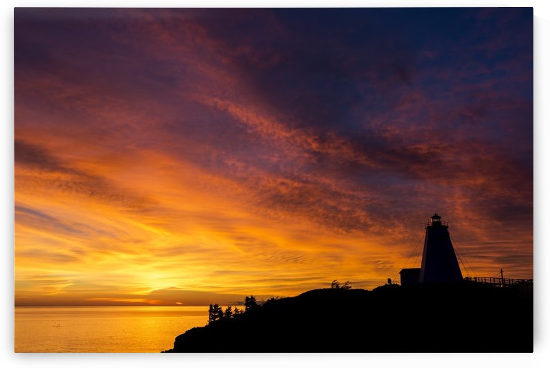 Silhouette of a lighthouse on a cliff overlooking a colourful reflected body of water with colourful dramatic clouds and blue sky; North Head, New Brunswick, Canada by PacificStock