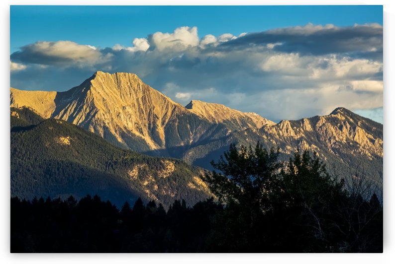 Dramatically lit mountain range at sunset with clouds and blue sky; Invermere, British Columbia, Canada by PacificStock