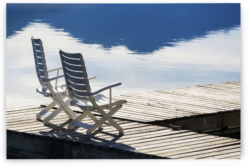 Two white wooden deck chairs on wooden boat dock reflecting in the water; Invermere, British Columbia, Canada by PacificStock