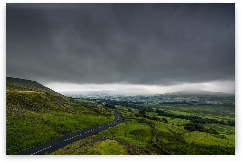 Dark storm clouds over a lush, green landscape and road; North Yorkshire, England by PacificStock