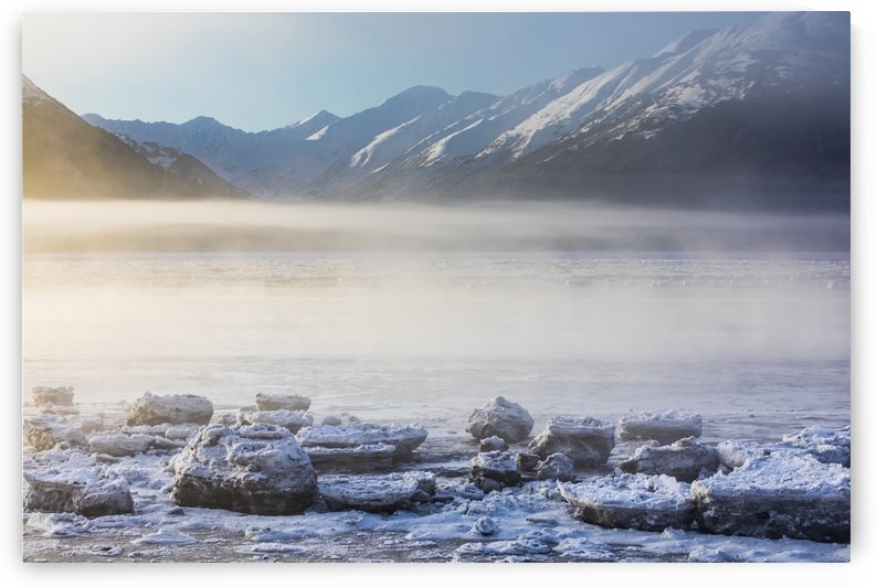 The sun shines through low altitude fog cast in warm light along Turnagain Arm and the Seward Highway, sea ice covering the ocean in the foreground, the Kenai Moutains revealed in the background, South-central Alaska; Alaska, United States of America by PacificStock