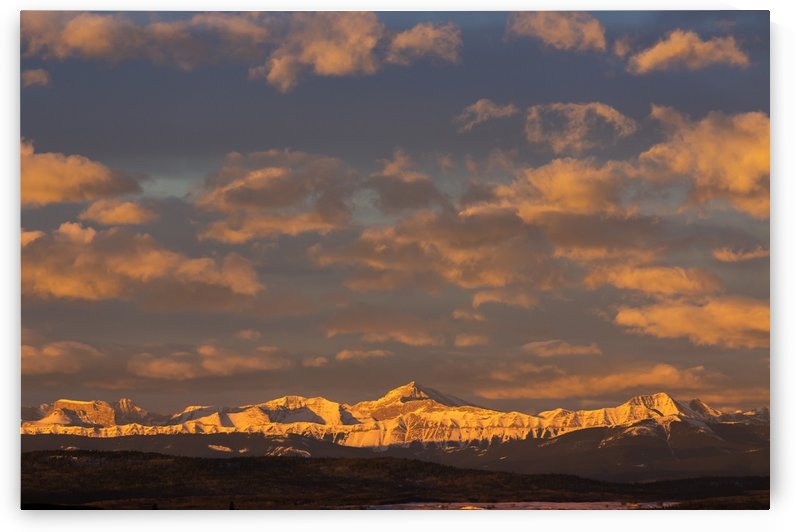 Glowing warmly lit snow covered mountain range and foothills with glowing clouds and blue sky at sunrise; Calgary, Alberta, Canada by PacificStock